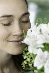 Young woman smelling bouquet of fresh flowers