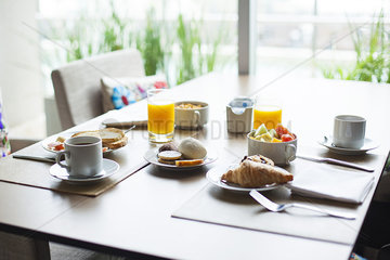 Breakfast of fruit and pastries on cafe table