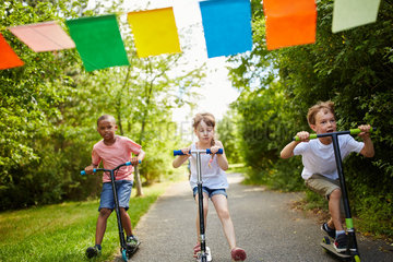Kinder machen Wettrennen mit dem Roller