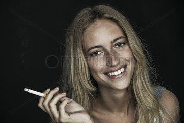 Young woman holding cigarette and smiling cheerfully  portrait