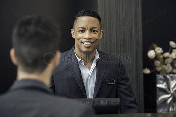 Man standing behind bank teller counter