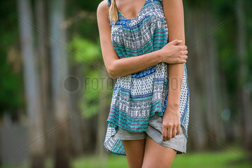 Young woman standing with arm folded across stomach  cropped