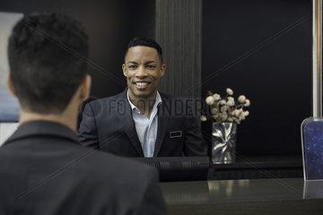 Hotel receptionist greeting customer
