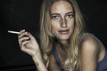 Young woman holding cigarette  portrait