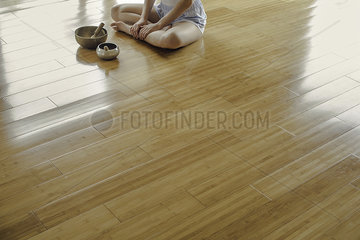 Woman sitting on floor by singing bowls
