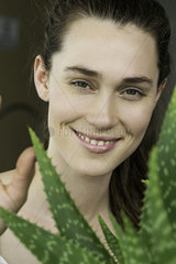 Young woman looking through aloe vera plant and smiling cheerfully