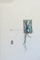 Electrical wires dangling from walls in unfinished building