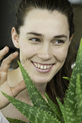 Young woman toucing aloe vera plant and laughing