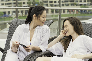Women in robes reclining and chatting outdoors