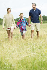 Family with one child on walk together in open field
