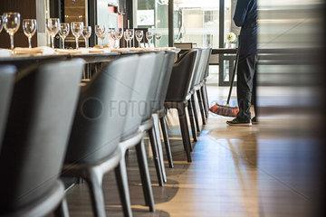 Person sweeping restaurant floor