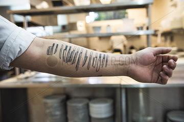 Kitchen utensils tattooed on arm