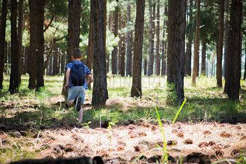 Boy running in woods