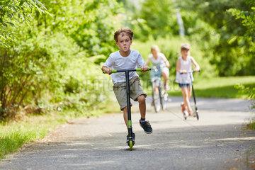 Aktive Kinder fahren mit dem Roller
