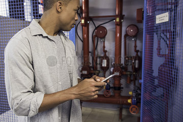 Man using mobile phone near fire protection sprinkler system