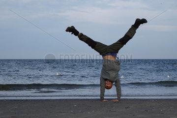 Wustrow  Deutschland  Junge macht einen Handstand am Strand