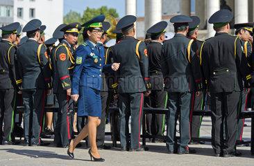 Frau in Uniform passiert maennliche Mitglieder der mongolischen Streitkraefte bei einer Parade