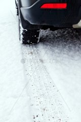 Spuren von Winterreifen im Schnee auf der Fahrbahn einer Strassuee