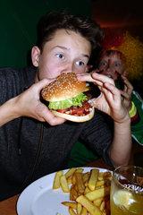 Berlin  Deutschland  Junge isst einen Burger mit Pommes Frites