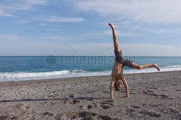 Taormia  Italien  Junge macht am Strand einen Handstand