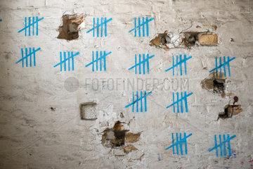 Strichliste in 5er Bloecken an einer Mauer