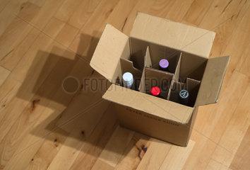 Weinkarton mit Weinflaschen auf einem Parkettfussboden