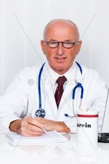 A doctor in his medical practice with stethoscope and laptopss