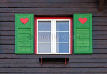 Herz-Symbole auf den Fensterlaeden eines Hauses