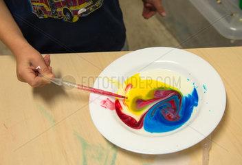 Kinder beim Spiel mit fluessigen Farben in einer Kindertagesstaette