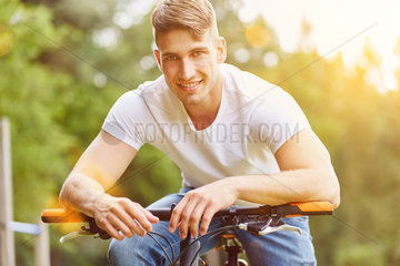 Junger Mann mit Fahrrad im Sommer
