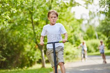 Ehrgeiziger Junge mit dem Roller