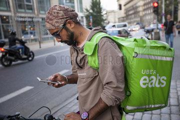 Migranten aus Asien arbeiten als Kurierfahrer fuer UberEats in Warschau