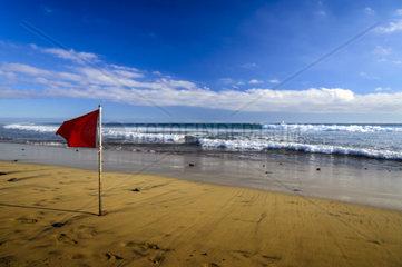 eine rote Fahne steht zum Zeichen des Badeverbotes am Strand