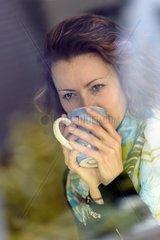 junge Frau mit einer Tasse Tee hinter einem Fenster