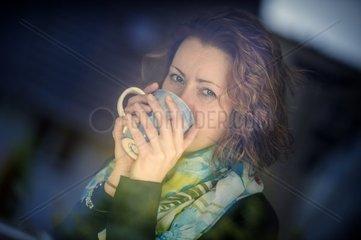 junge Frau ist erkaeltet und trinkt Tee
