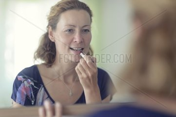 young woman stands in front of the mirror and paints her lips