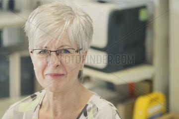 eine freundliche Dame sitzt an einem Schreibtisch