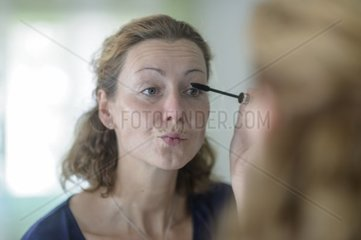 young woman stands in front of the mirror and tuscht the eyelashes
