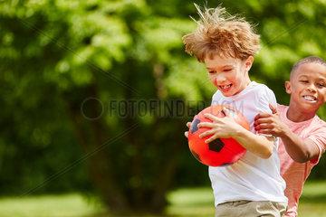 Zwei Jungen raufen um den Ball