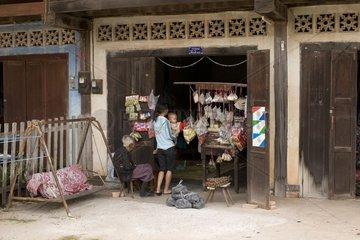 Aeltere Frau verkauft Suessigkeiten und Kekse an Mutter mit Kind / Savannakhe