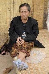 Aeltere Frau sitzt vor ihrem Haus / Savannakhet / Laos / SUEDOSTASIEN-REISE