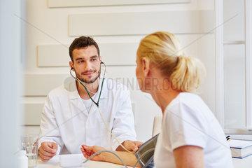 Arzt misst Blutdruck zur Kontrolle