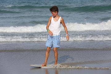 Cocoa Beach  USA  Junge surft am Strand im seichten Wasser