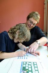 Berlin  Deutschland  Kinderdorf-Mutter hilft bei den Schularbeiten