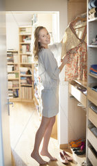 beautiful young woman choosing her clothes in the morning on a s