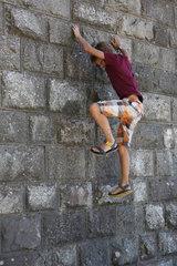 Torre Alfina  Italien  Junge versucht in Sandalen an einer Hauswand hochzuklettern