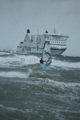 Rostock  Deutschland  Surfer in hohen Wellen vor Schiff