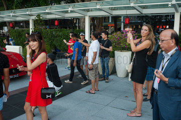 Singapur  Republik Singapur  Menschen fotografieren einen Ferrari in Marina Bay
