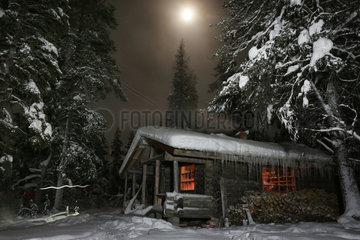 Aekaeskero  Finnland  eingeschneite Holzhuette bei Mondschein