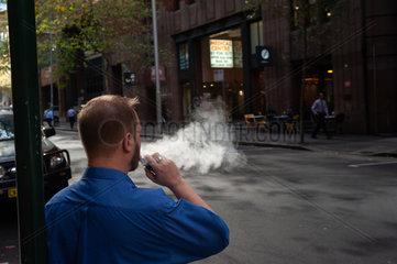 Sydney  Australien  Ein Mann raucht eine elektrische Zigarette / E-Zigarette